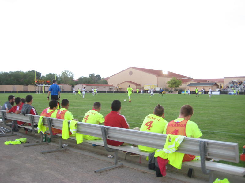 The Sol bench watches as the teams battle on the field.