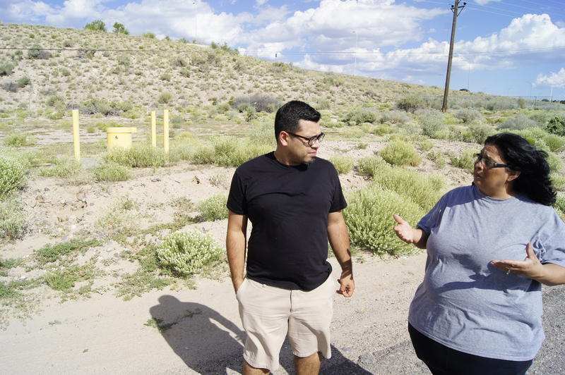 Juan Reynosa of the Southwest Organizing Project and Esther Abeyta of the San Jose Neighborhood Association stand at the site of the proposed road project. To the left is a well that is part of the South Valley Superfund site.