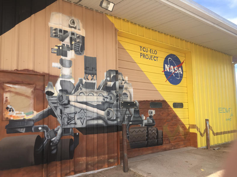 Mural of a rover painted on the side of the main Mars yard warehouse.