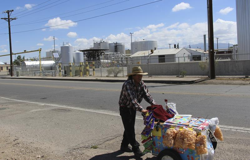 A vendor pushes his cart past the Western Refining asphalt plant on Second St SW in Albuquerque.