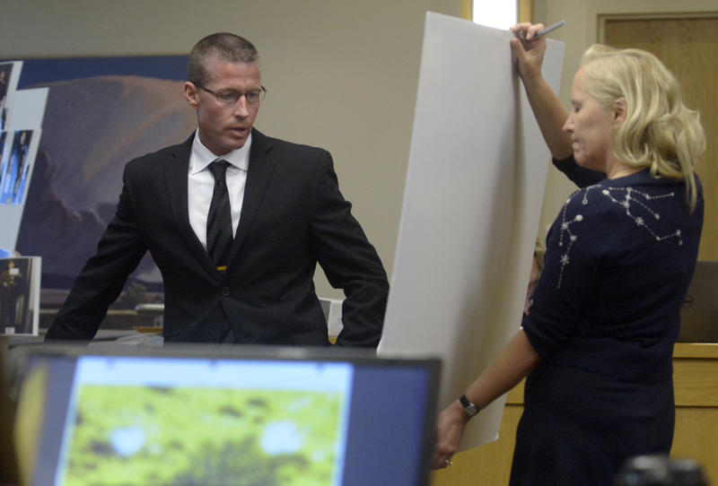 Sgt. James Fox points out officers on a map of the scene that prosecutor Randi McGinn holds up.