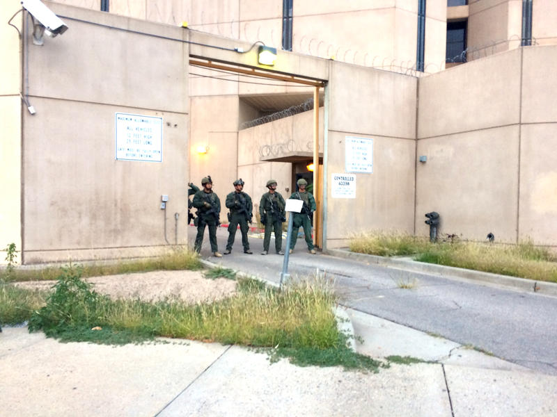 The protest makes its way to the police station. Turning the corner on Fifth Street, tactical officers armed with what looked like rifles stood in the doorway of a rear exit. More could be seen looking down through binoculars from rooftops.