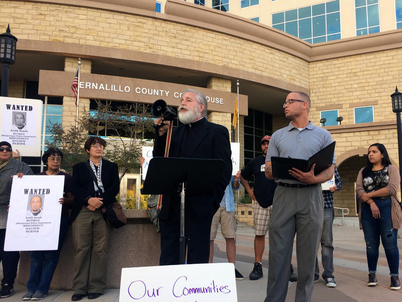Father Frank Quintana speaks to a small crowd gathered in front of the Bernalillo County Courthouse.