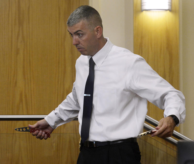 Albuquerque Police Sgt. Richard Ingram shows the jury how James Boyd would pull out two knives from his pockets.