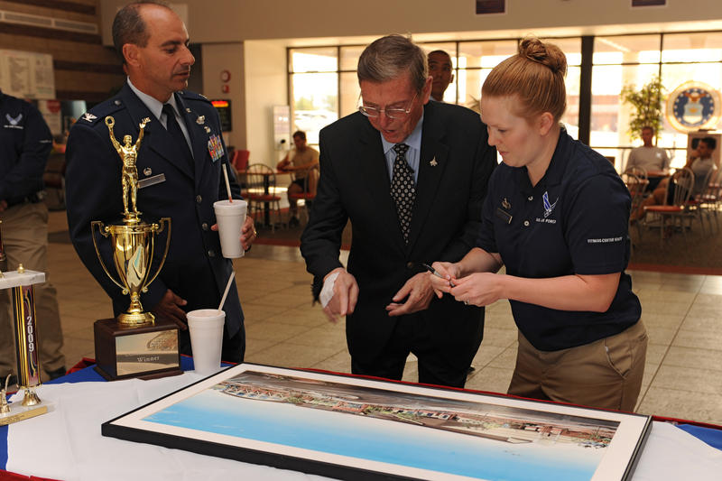 Retired Sen. Pete Domenici, signs a painting of the Domenici Fitness and Sports Center Sept. 18, 2009, at the official renaming of the Holloman Fitness and Sports Center.