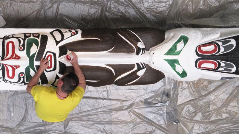 A master carver restoring the Smith Family Totem Pole earlier this year at UNM