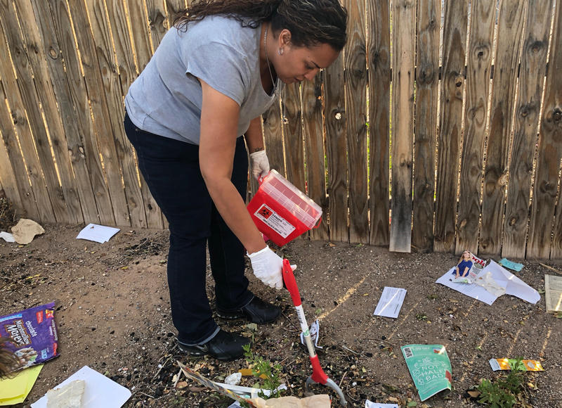 Sarah Ochoa picks up needles with a grabber as a part of the International District Healthy Communities Coalition's new project.