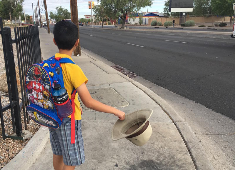 Masihullah Naseri waits to cross Central Avenue in southeast Albuquerque on his way to summer school.
