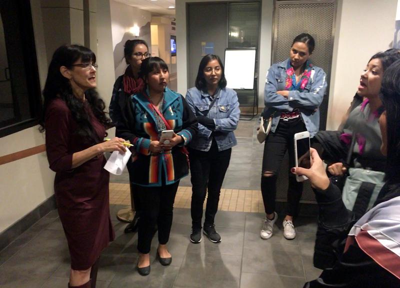 APS board member Peggy Muller-Aragón (left) listens to young women demanding that a Cibola high school teacher be fired after a racist incident.