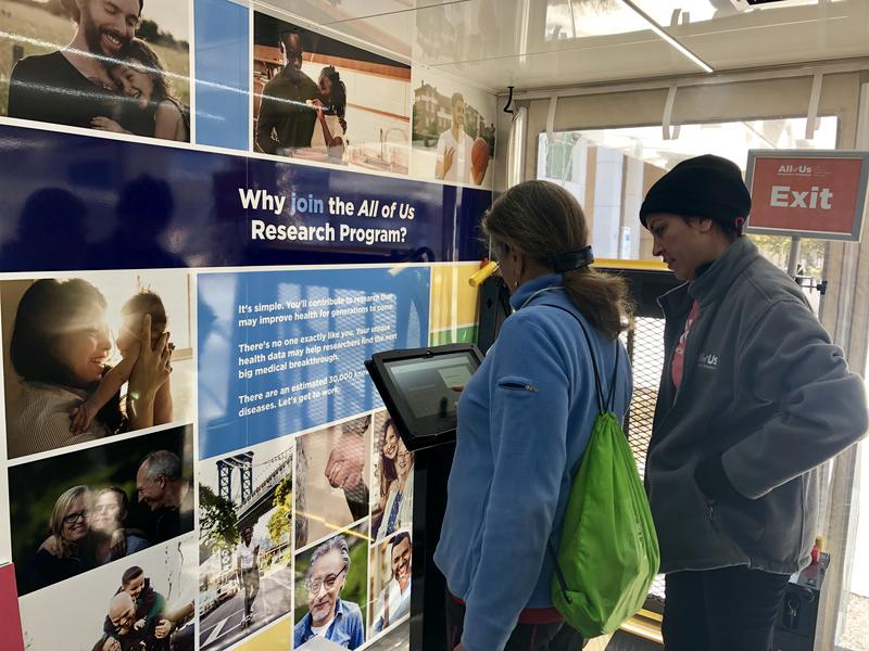 A volutneer speaks with a participant at the National Institutes of Health's All of Us project.