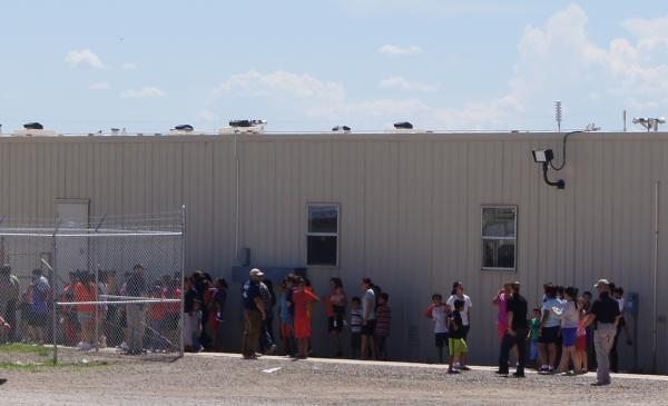 Women and their children line up at the Artesia immigrant detention center, as protesters gathered outside the facility