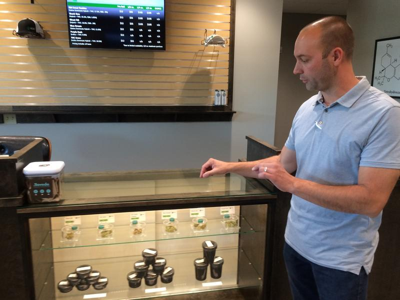 Aaron Swan, general manager of Silver State Relief, shows some of their cannabis products inside the display case.