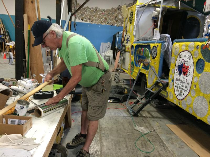 """Tim Kelly works on """"The Babe,"""" a multi-passenger art car with a wheelchair lift. Kelly stays at Mobility Camp during the festival, which provides support services to the physically impaired."""