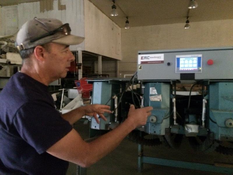 John Snyder points to a machine that automatically weighs 50-pound bags of onions for shipment.