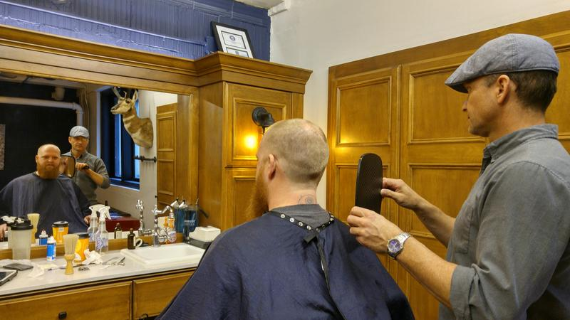 Beautiful Bearded Man is a barber shop located inside the basement. Barber Don Anderson is showing his customer his new look.