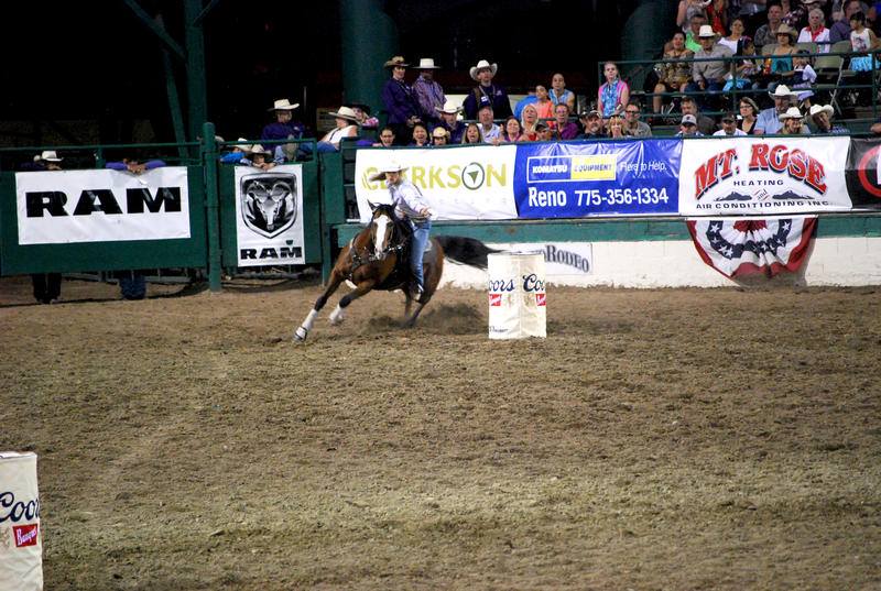 The crowd reacts as a contestant rounds the final barrel in the Women's Barrel Racing event.