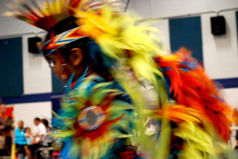 "A performer dances by in a blur in his traditional regalia. Importantly, one does not use the word ""costume"" to describe this traditional dress because a costume assumes another identity, whereas this regalia is part of a dancer's identity and culture"