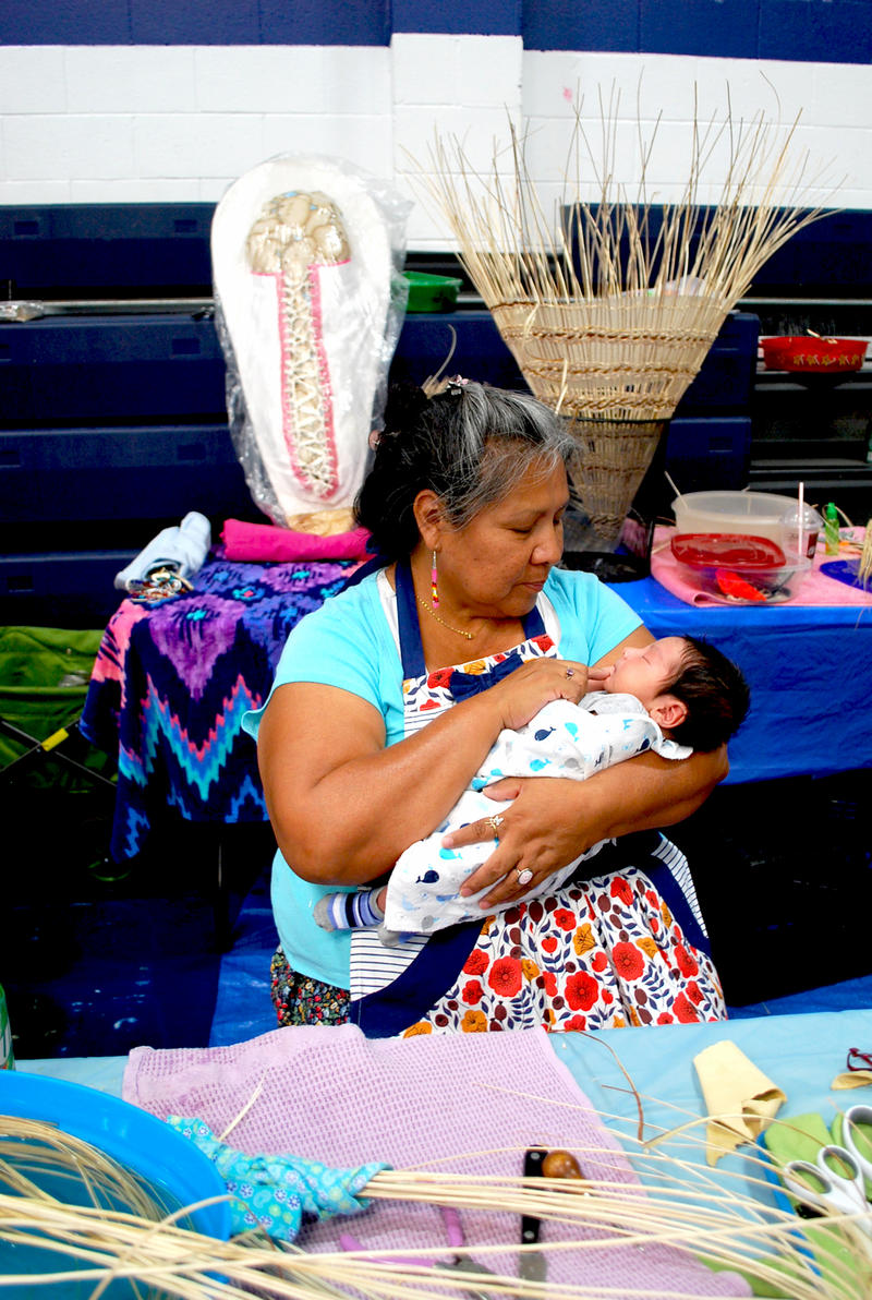 Tammie Henry holds her nine-day-old grandson, Louis Benjamin. Behind her on the left is a traditional cradleboard for infants like Louis, and in the foreground is a cradleboard she is working on for him. Tammie is a member of the Great Basin Native Basket