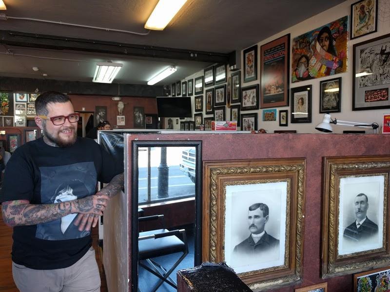 Albert Rivas, gerente del salon de tatuajes A Toda Madre, muestra su estación de tatuajes replena de sus creaciones artísticas y retratos que encontró en una venta de propiedades.