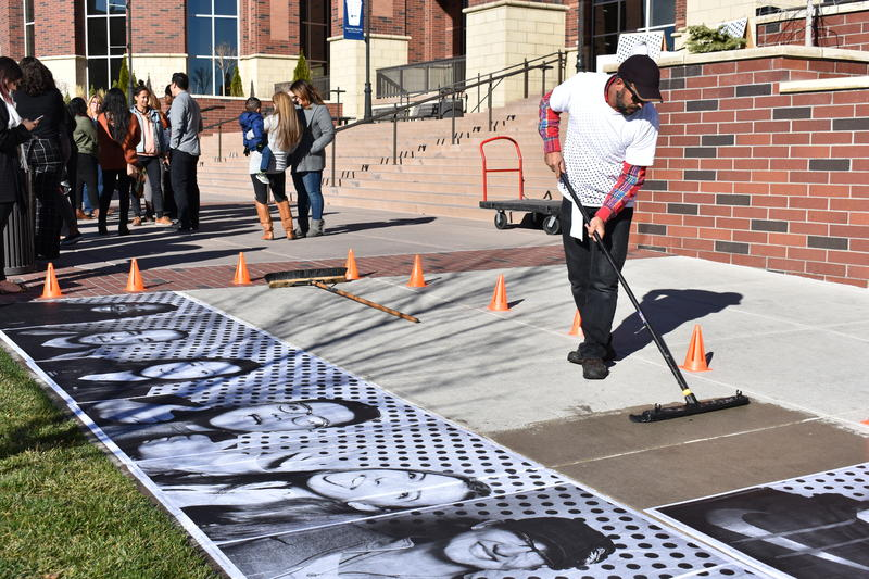 An artist with the Inside Out Dreamers Project pastes photos of UNR students on the sidewalk who had their photos taken to show solidarity with Dreamers.