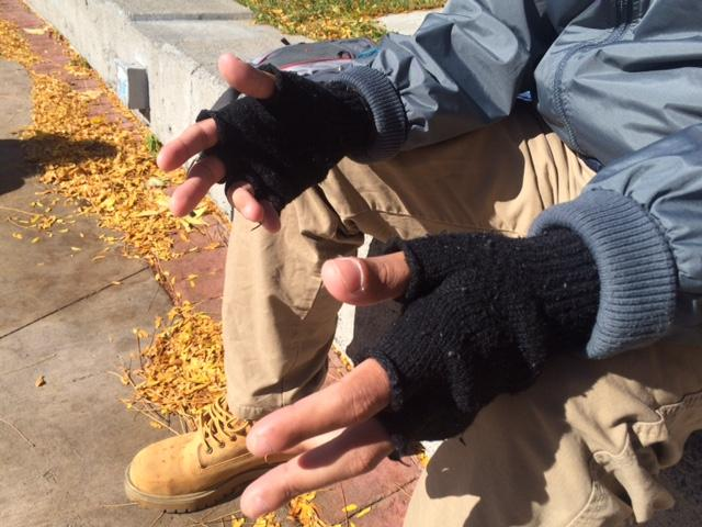 On a cold day, Derek Rivera warms up in the sun while waiting to go back to Reno's homeless shelter.