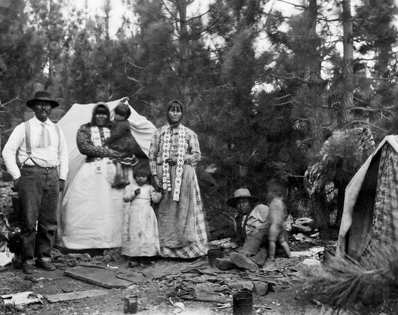 Washoe tribal members Billy Merrill, Maggie Merrill, Minnie George, and one Arm George in a camp at Lake Tahoe, ca. 1910-1920.