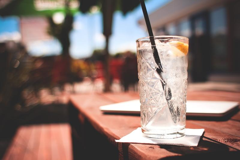 A close up image of a drink with a straw on a wooden table on an outside patio.