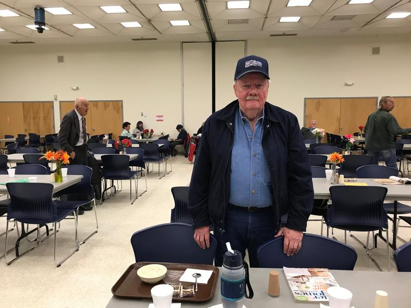 A senior stands at a table with food in front of him.