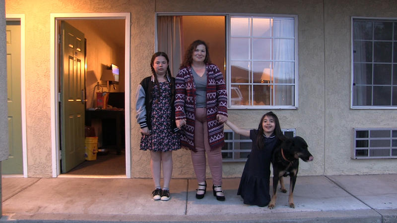A women, her two daughters, and their dog, stand outside their motel room
