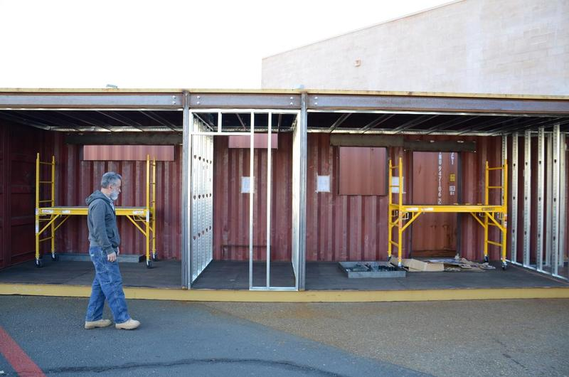 Masih Madani walks in front of one shipping container, one-half of the future home.