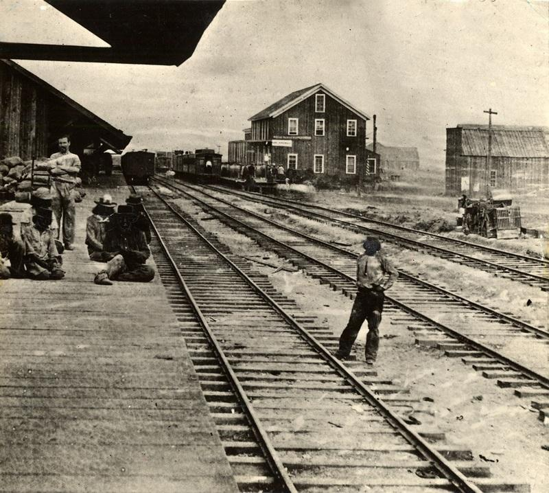 A black and white image of Reno's original railroad depot in 1868, where some figures stand by three sets of tracks.