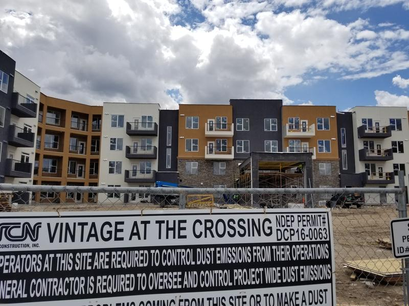Image of apartment complex behind chainlink fence and construction sign.