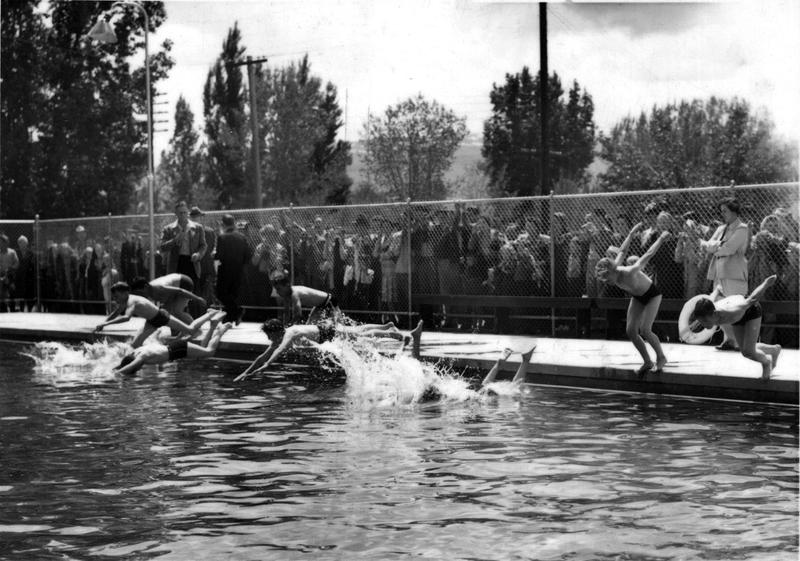 A black and white photo of several people jumping into a pool in Reno.