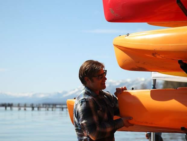 A man inspects a rack of kayaks on a Lake Tahoe shore.