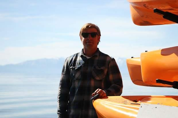 A man stands next to a rack of kayaks on a Lake Tahoe shore.