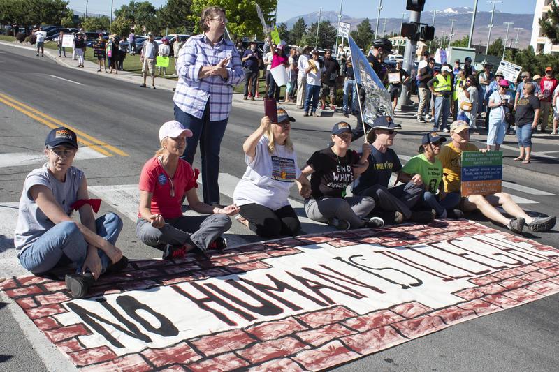 Manifestantes sientan en el medio de la calle.