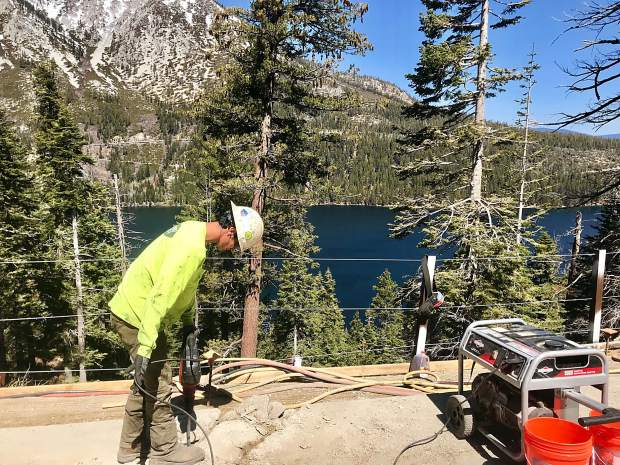 A worker stands on the side of the road above Emerald Bay holding machinery.
