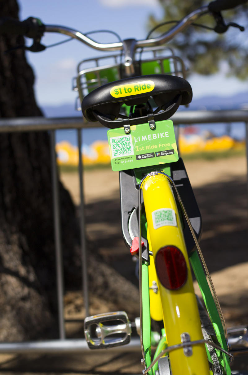 "The back of a yellow and green Lime Bike with a small sign on the back saying ""1st ride free"" and a scannable code."