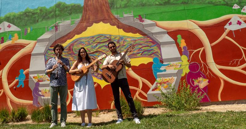 Three musicians stand in front of a grafitti wall with instruments