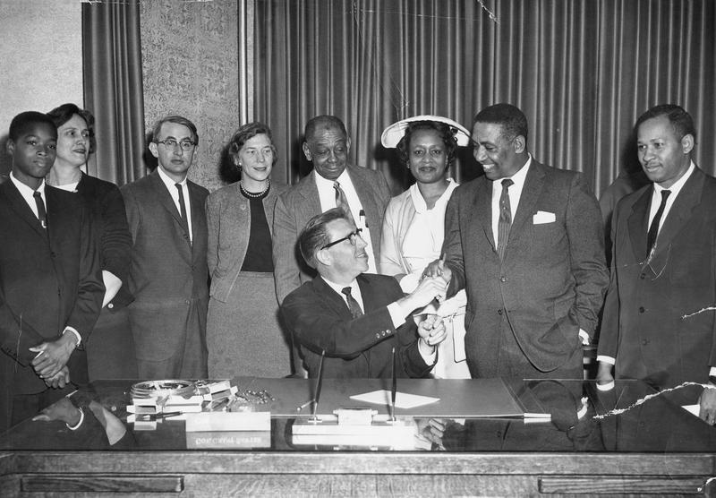 A black and white photo of a man sitting at a desk turned to his left, shaking the hand of a man standing. Seven other people stand behind the two men shaking hands, all formally dressed.