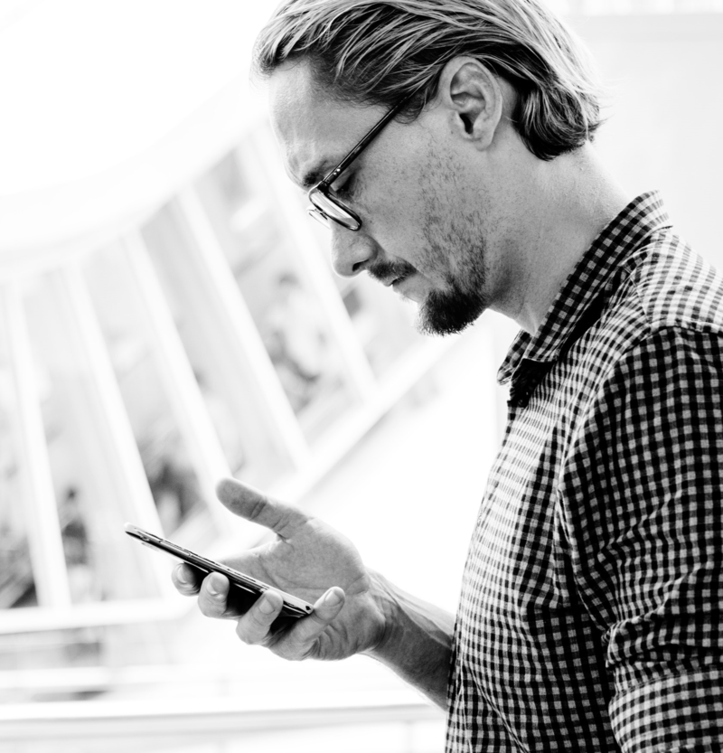 A black and white photo of a man holding a cellphone and looking down at the screen.