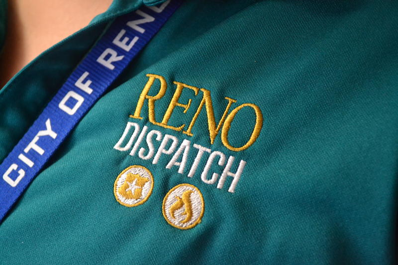 "A close-up of a green t-shirt with a logo reading ""RENO DISPATCH"" in gold and white letters. Below the lettering, are two circular gold embloms, one with a flame inside and the other with a shield."