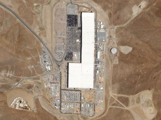 A bird's eye view of a large, white factory, surrounded by brown land and dirt roads.