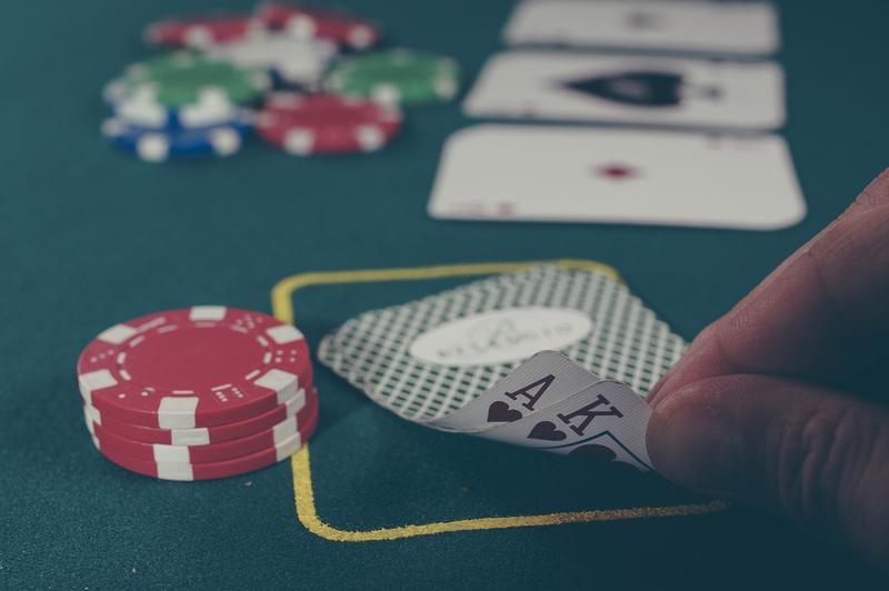 A photo of a green casino gaming table with multicolored chips and a hand turning over an Ace card and a King card.