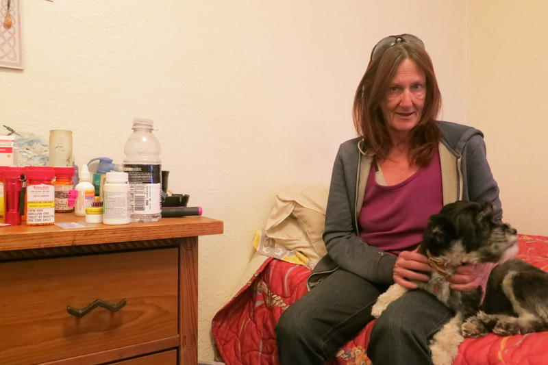 A woman and a small dog sit on a bed inside a motel.