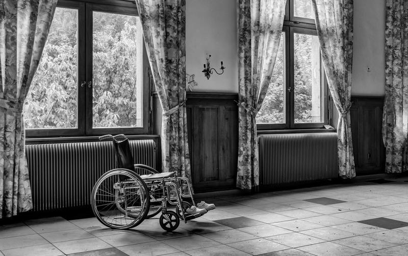 Black and white photo of a wheelchair in a room.
