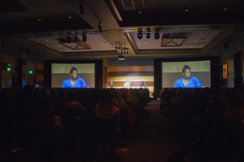 Two screens project a woman's image in a crowded ballroom.
