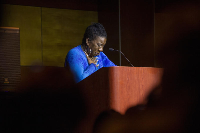 A woman cries while standing behind a podium.