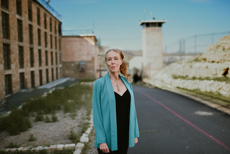 A blond woman stands on the grounds of a prison, between a guard tower and a mulit-level brick prison buildilng.