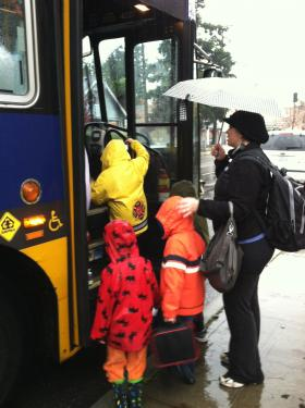 Woman with unbrella helps kids get on a bus